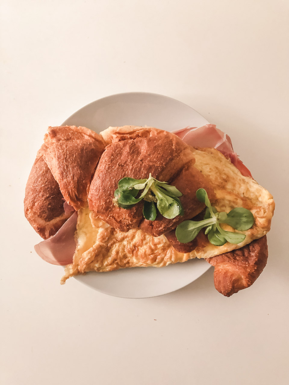 A croissant stuffed with an omelette on a plate