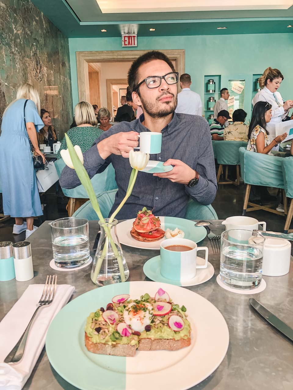 A man drinking coffee and eating breakfast at The Blue Box Cafe in New York City