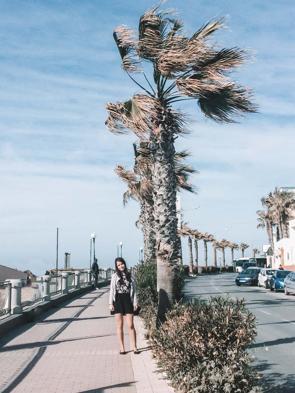 A girl standing on a promenade lined with palm trees in Bugibba, Malta