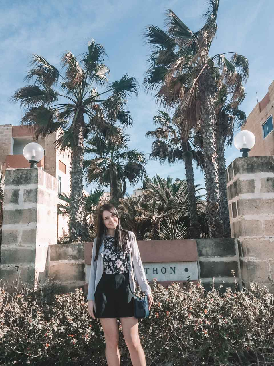 A girl standing next to palm trees and a traditional house in Bugibba, Malta