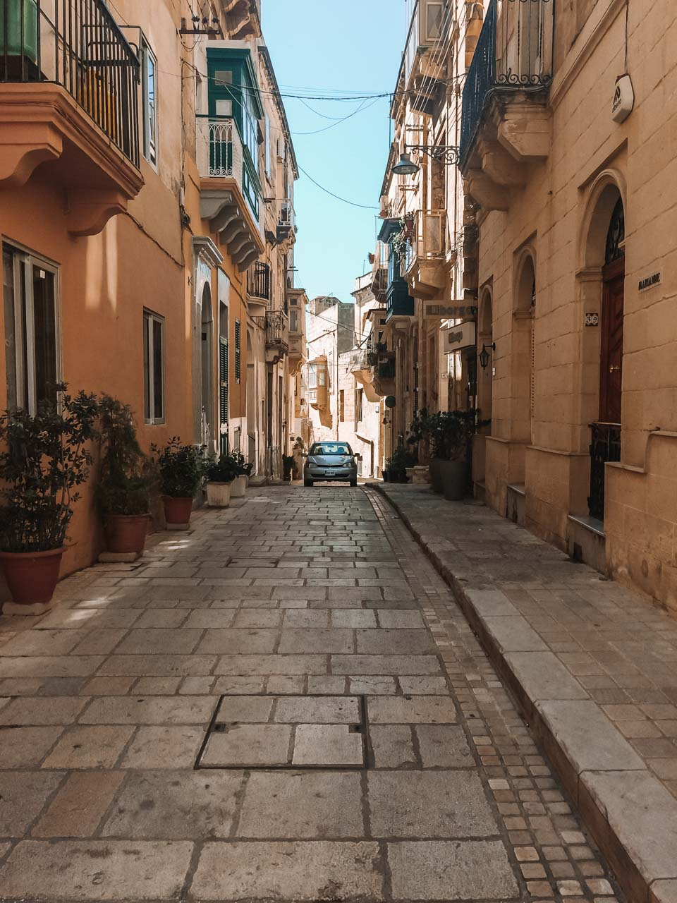 A car driving in a traditional alley in Birgu, Malta