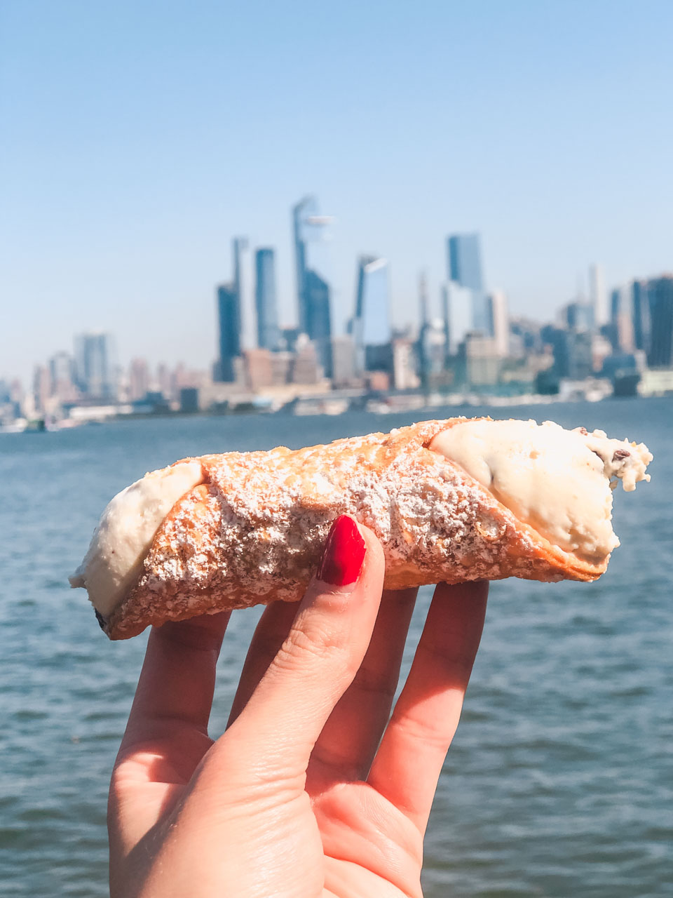 A girl holding a cannoli from Carlo's Bake Shop with the Manhattan skyline in the background