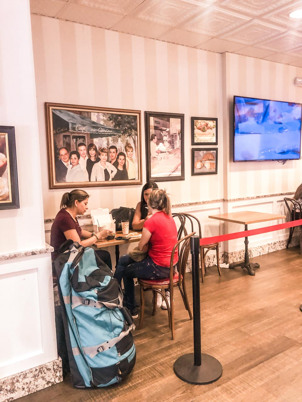 Three women having cakes and coffee at Carlo's Bakery with the Valastro family photo on the wall behind them