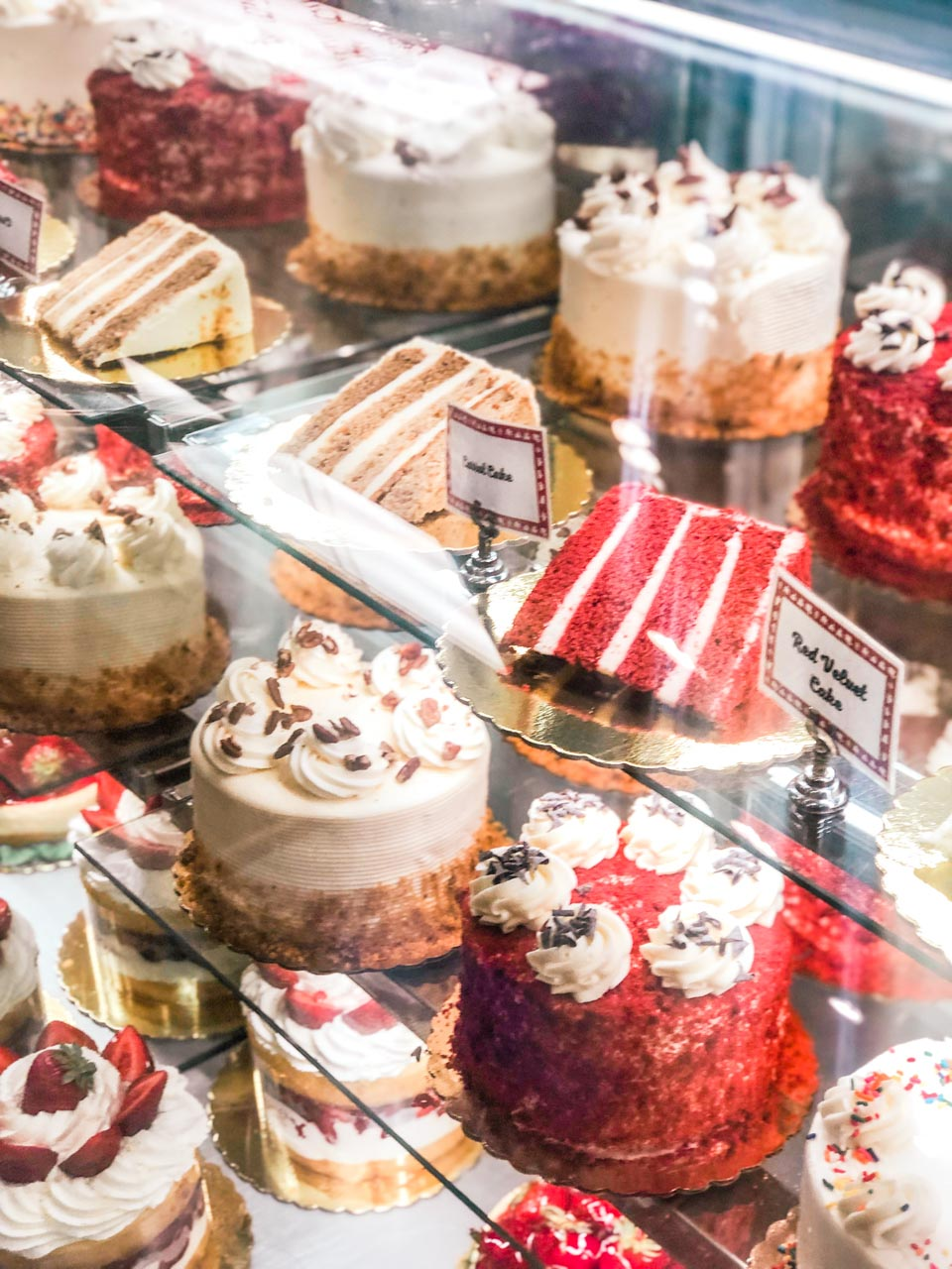 Carrot cake and red velvet cake on display inside Carlo's Bakery in Hoboken, New Jersey