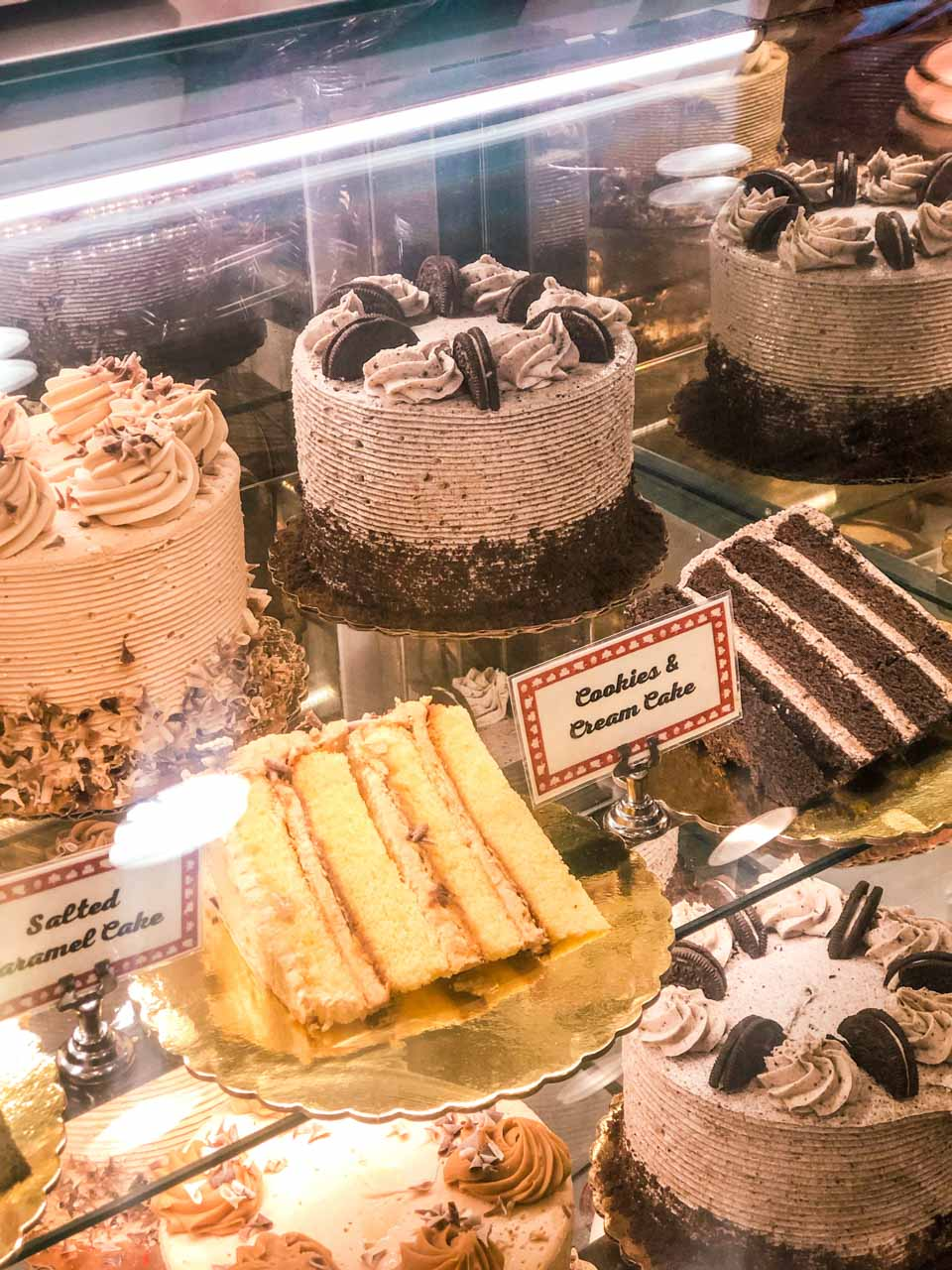 Salted caramel cake and cookies & cream cake on display inside Carlo's Bakery in Hoboken, NJ