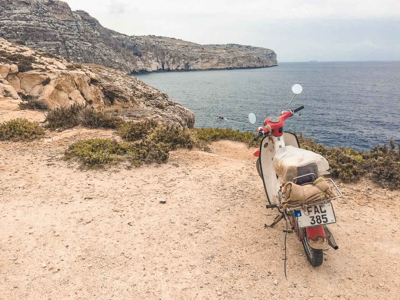A scooter parked close to the edge of the Blue Grotto, Malta
