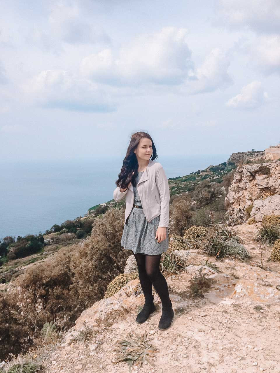 A girl standing close to the edge of the Dingli Cliffs in Malta