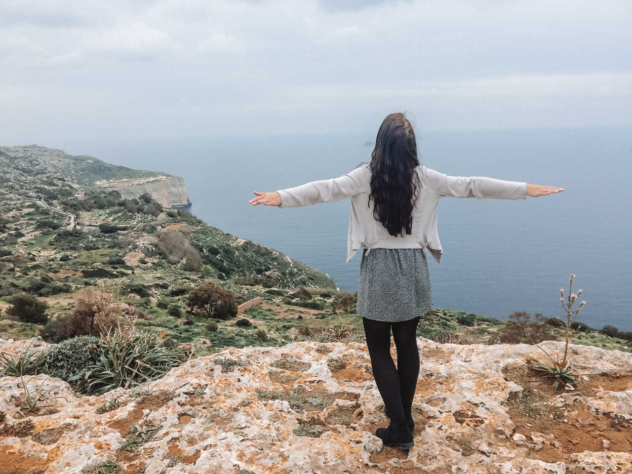 A girl standing close to the edge of the Dingli Cliffs, Malta