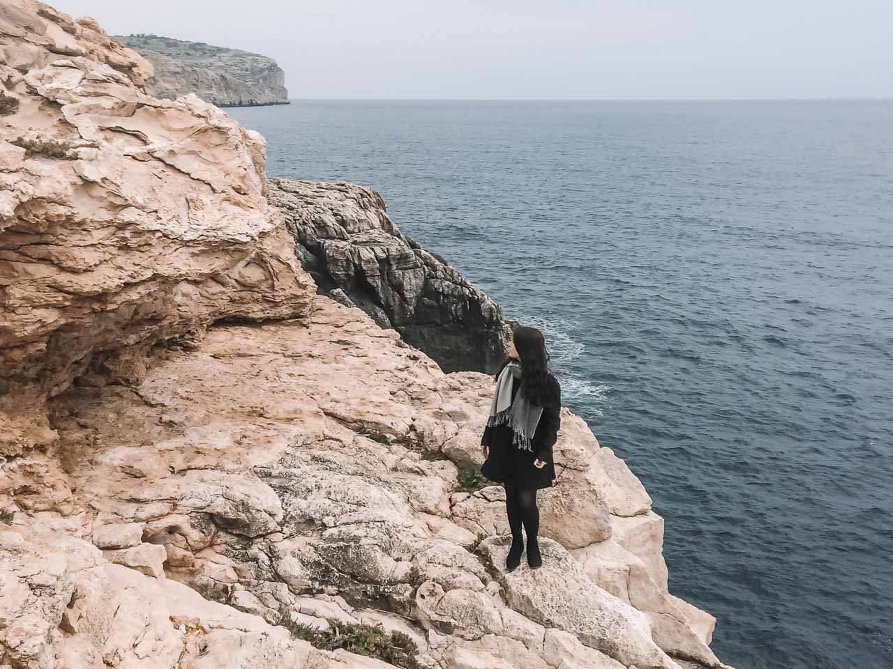 A girl in a coat standing close to the Blue Grotto, Malta