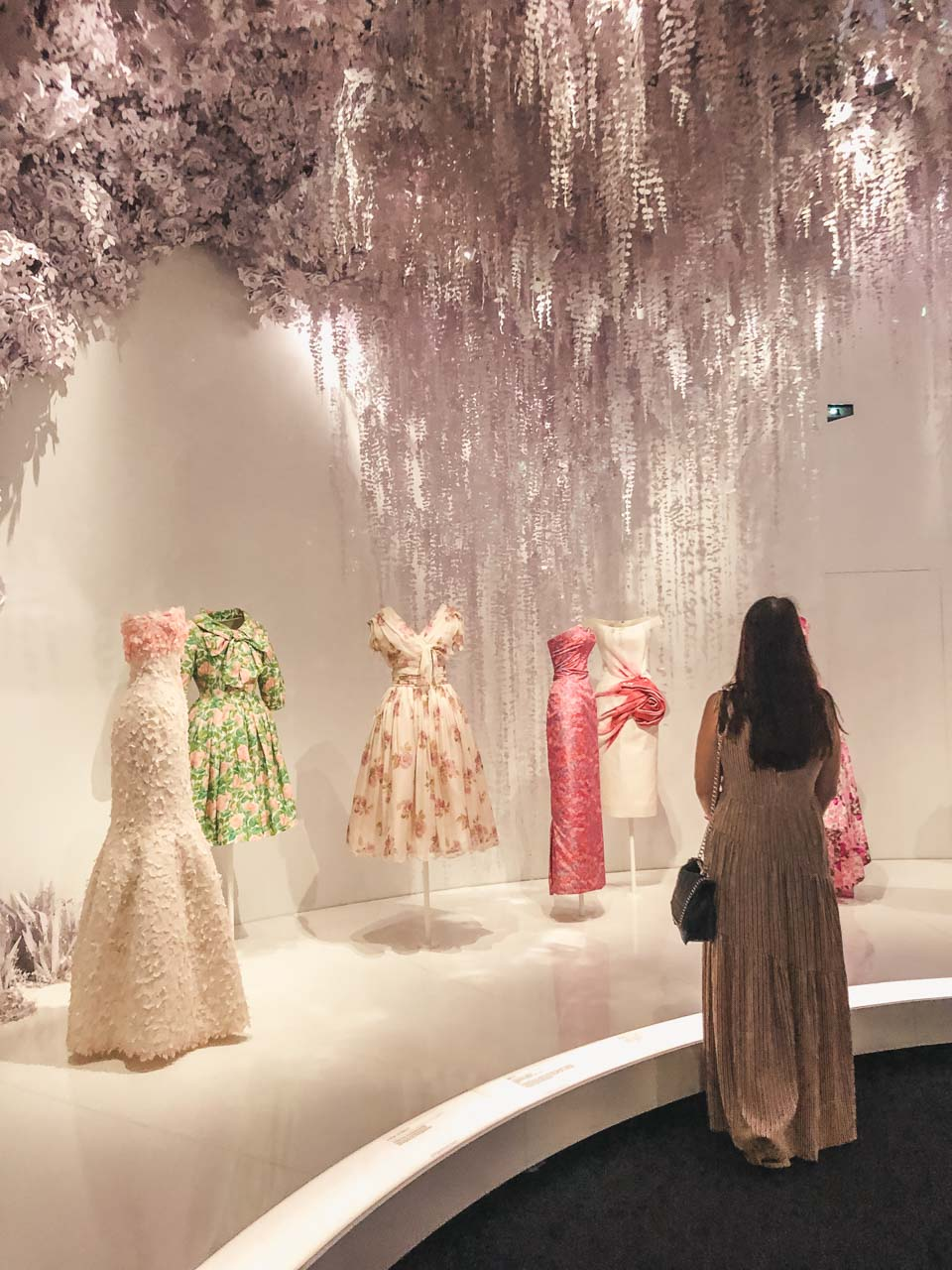 A girl standing in the garden room of the Dior exhibition at the Victoria and Albert Museum in London, looking at dresses