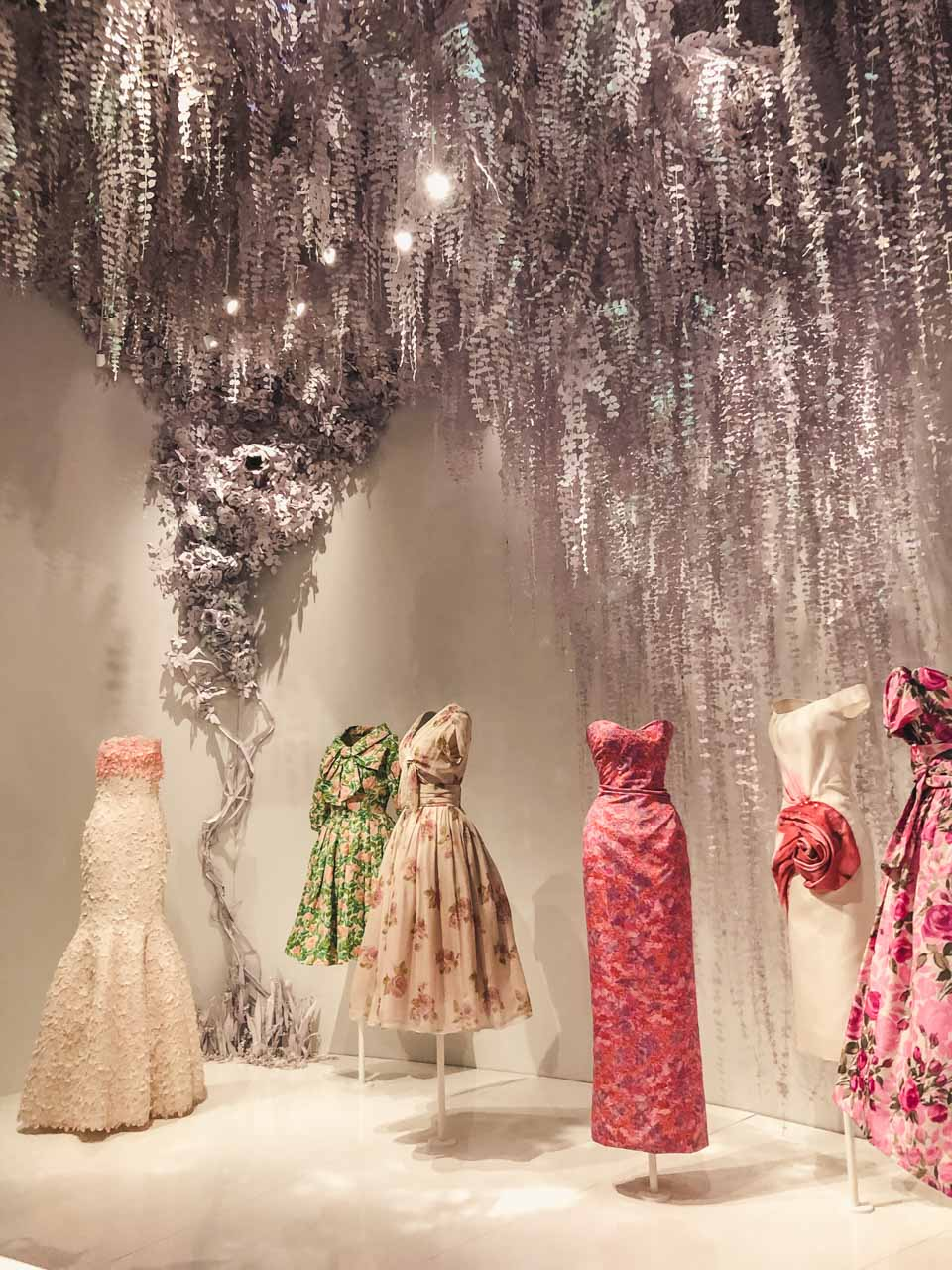 Dior gowns on display in the garden room of the Dior exhibition at the Victoria and Albert Museum in London