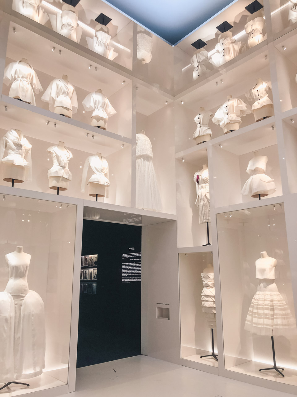 A floor-to-ceiling display of white garment prototypes at a Dior atelier at the Victoria and Albert Museum in London