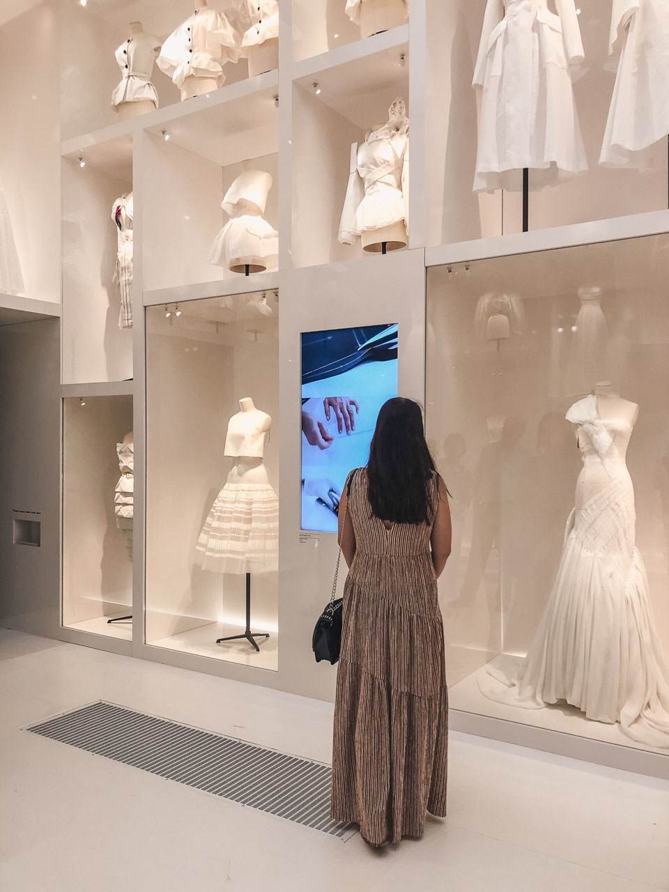 A girl looking at a floor-to-ceiling display of white garment prototypes at a Dior atelier at the Victoria and Albert Museum in London