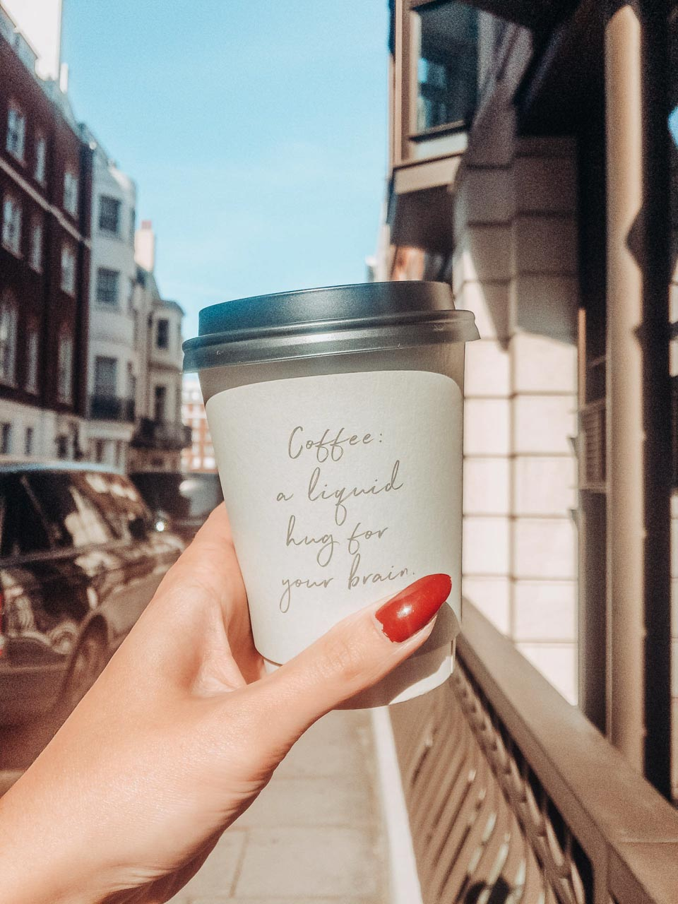 A girl holding a cup of coffee standing in a street in Mayfair, London