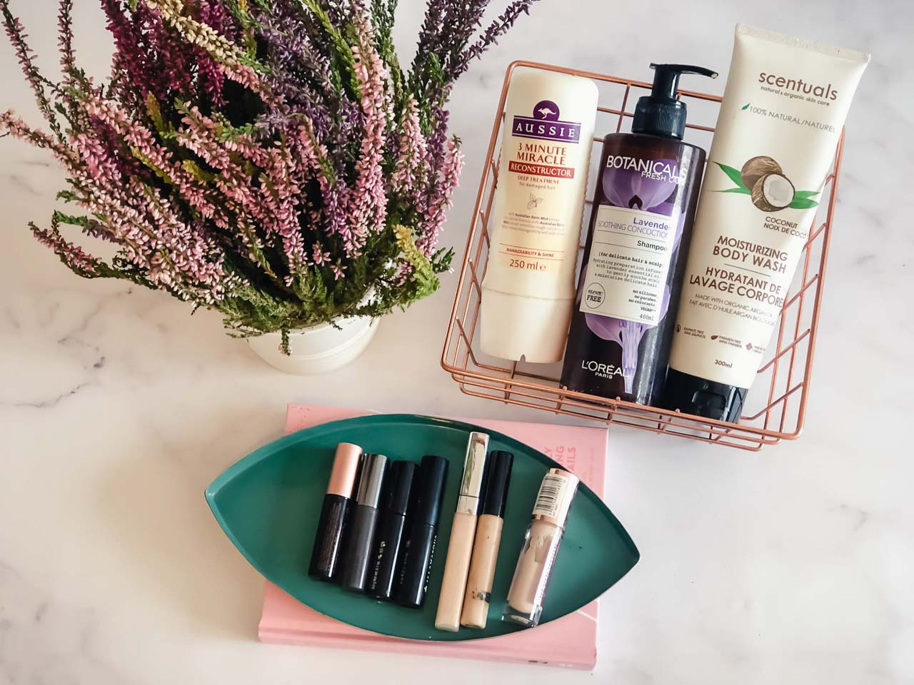 Makeup, skincare, hair and bath products displayed on a marble desk next to a heather plant