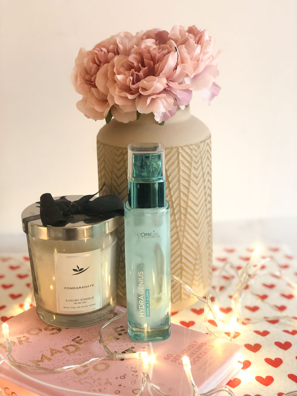 L'Oreal Hydra Genius moisturiser on a desk next to a candle and a vase with peonies