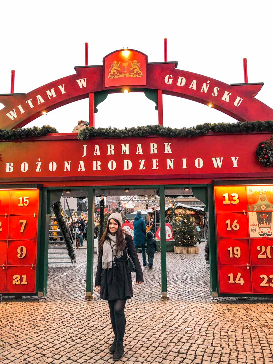 A girl standing in front of the Advent Gate at the Christmas market in Gdańsk