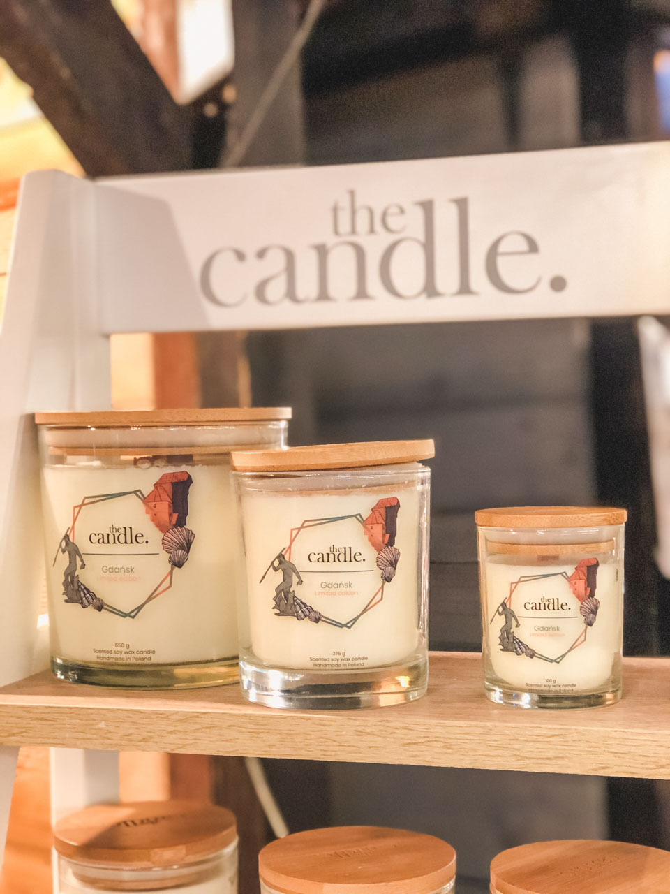 Three candles displayed on a wooden shelf