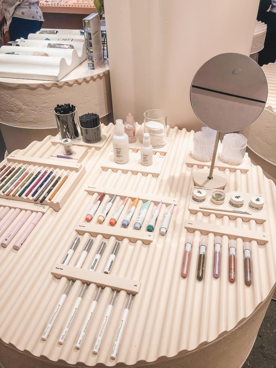 Cosmetics placed on a ribbed podium inside the Glossier flagship store in New York City