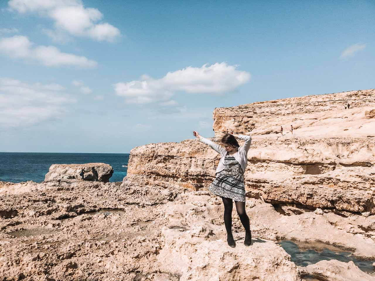 A girl in a patterned dress standing next to the Azure Window, Gozo