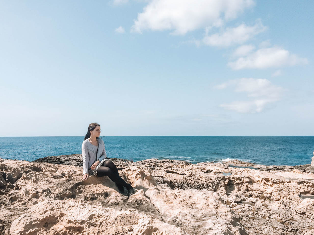 A girl sitting on rocks where the Azure Window in Gozo used to be