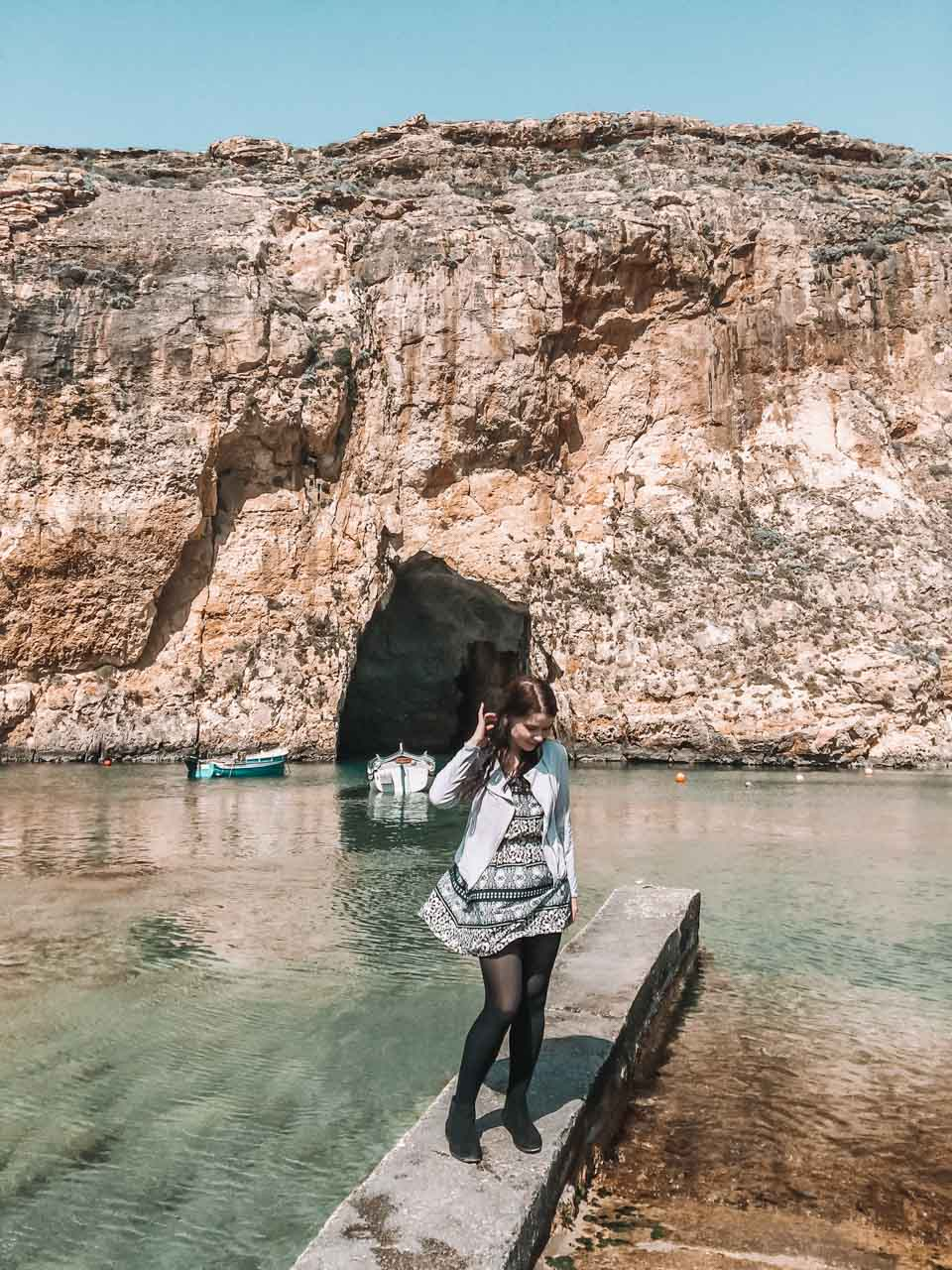 A girl in a patterned dress standing on a tiny pier in Gozo