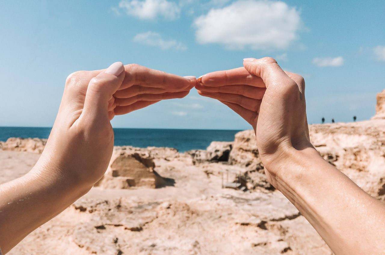 Two hands touching to recreate the shape of the Azure Window in Gozo