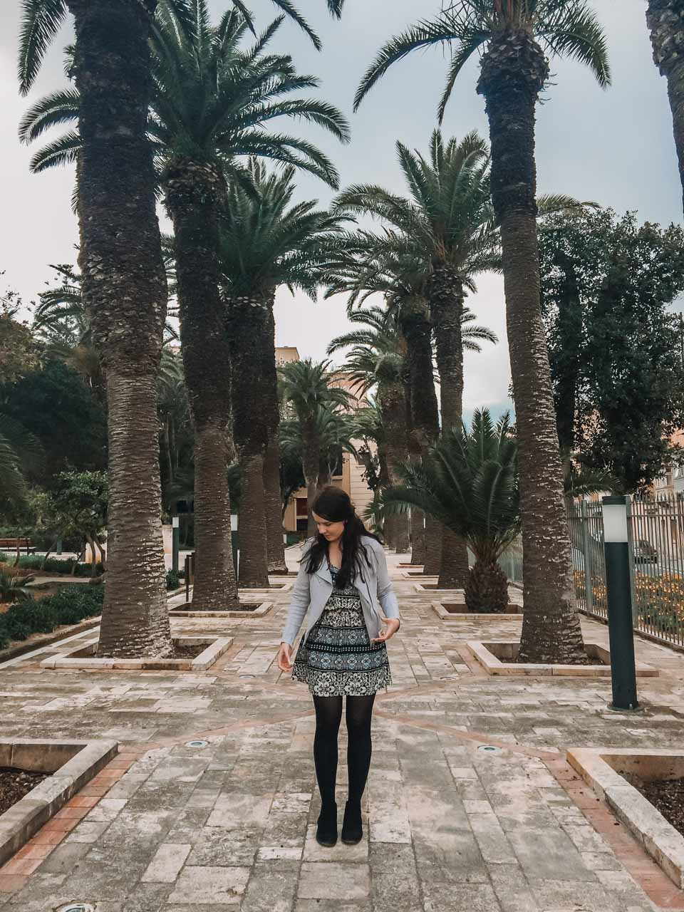 A girl in a patterned dress standing in the Villa Rundle Gardens in Gozo