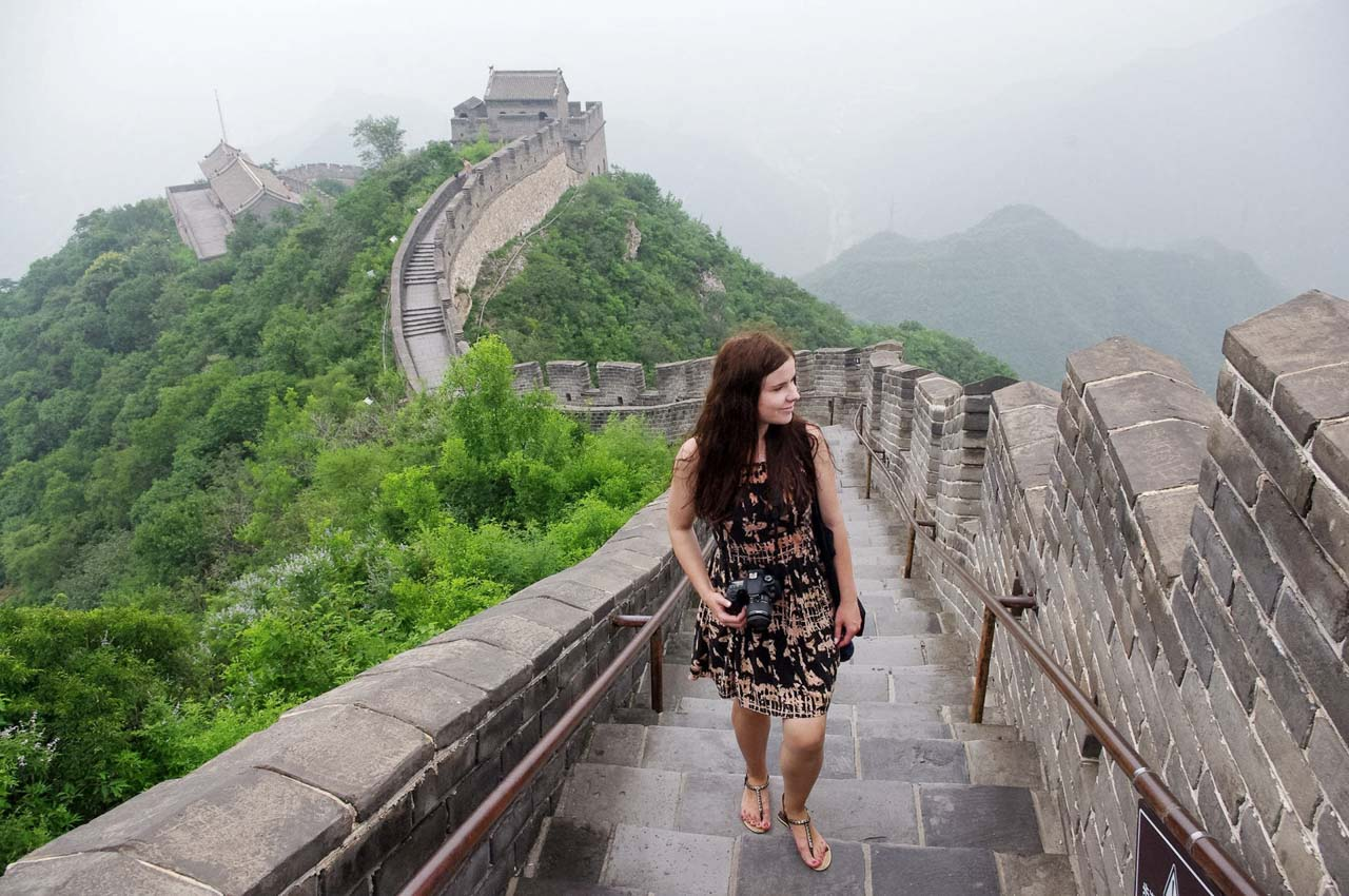 A girl with a camera round her neck standing on the Great Wall of China