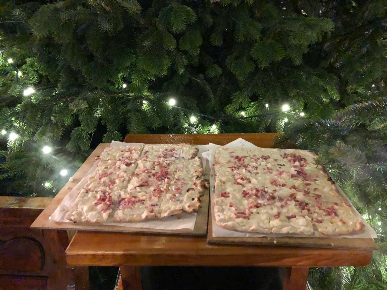 Flammkuchen in front of a Christmas tree at a Christmas market in Hamburg