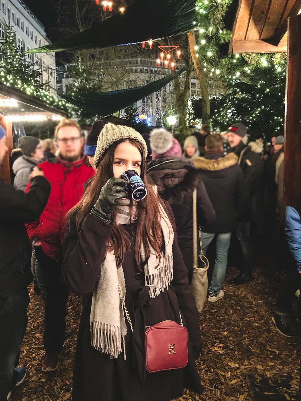 A girl holding a mug of mulled wine