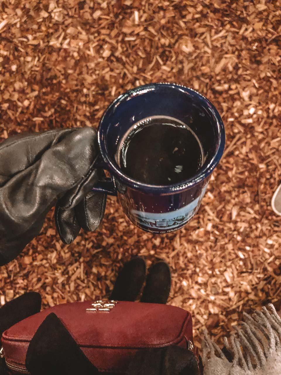 A girl holding a mug of mulled wine at a Christmas market in Hamburg