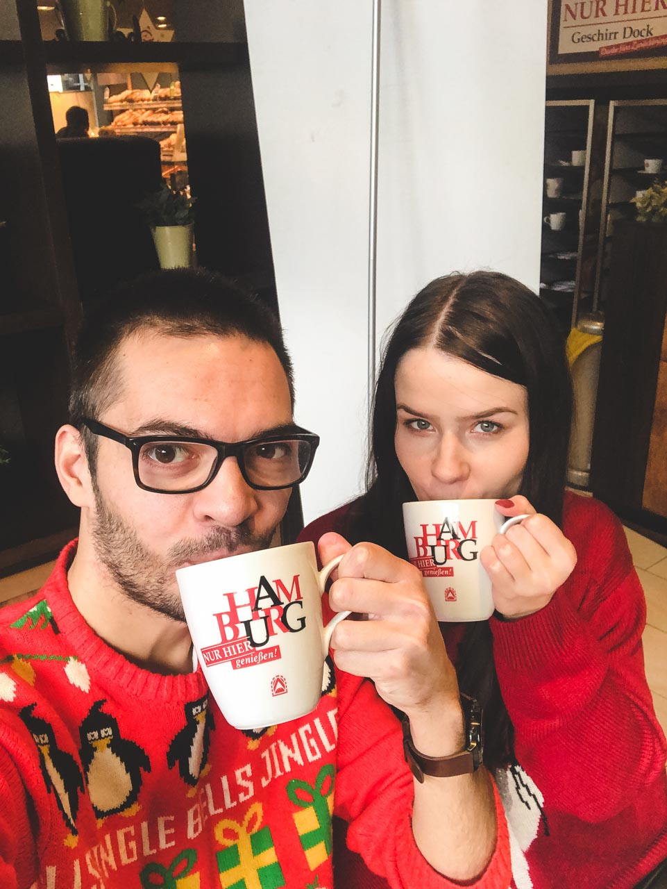 Two people drinking coffee wearing Christmas jumpers