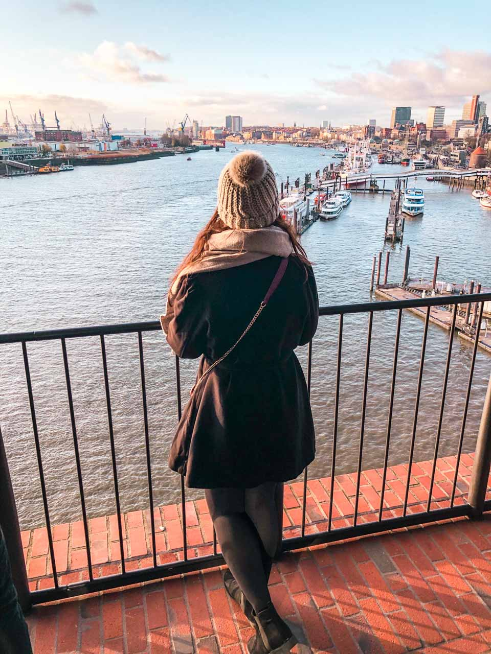 A girl in a black coat admiring the view from Elbphilharmonie Plaza in Hamburg