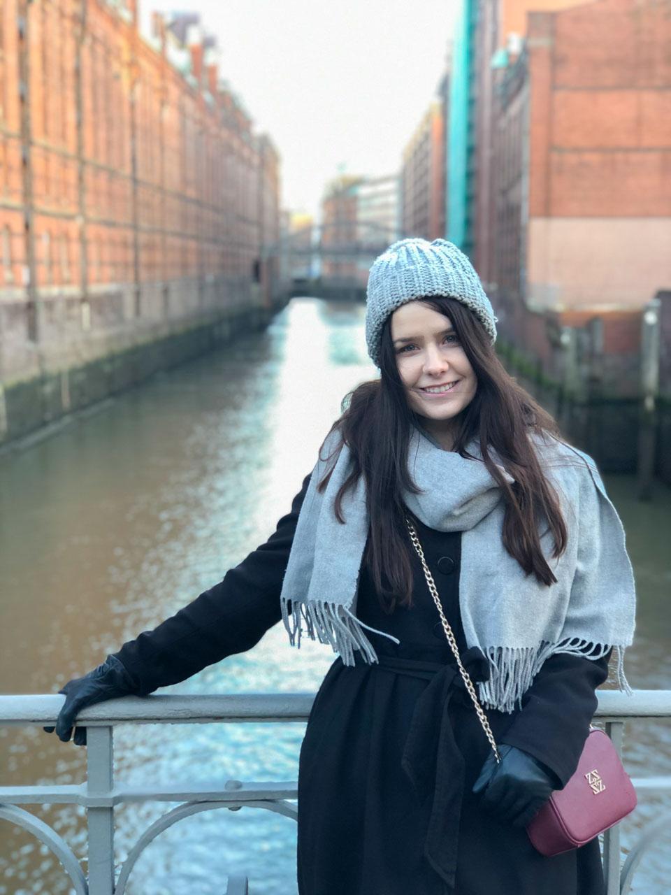 A girl in a black coat standing in Speicherstadt in Hamburg