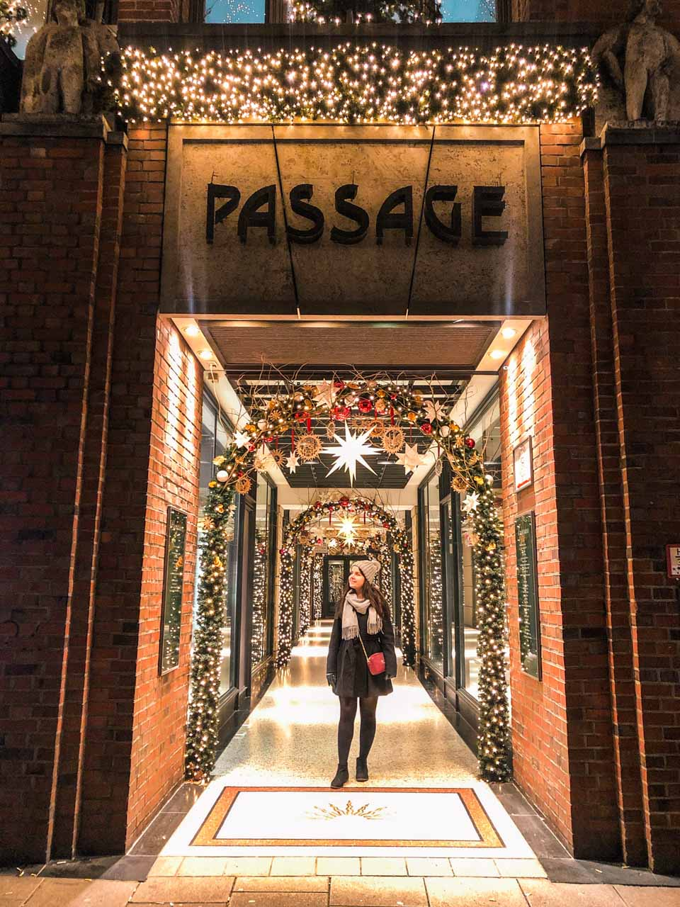 A girl standing in a passage decorated with Christmas lights