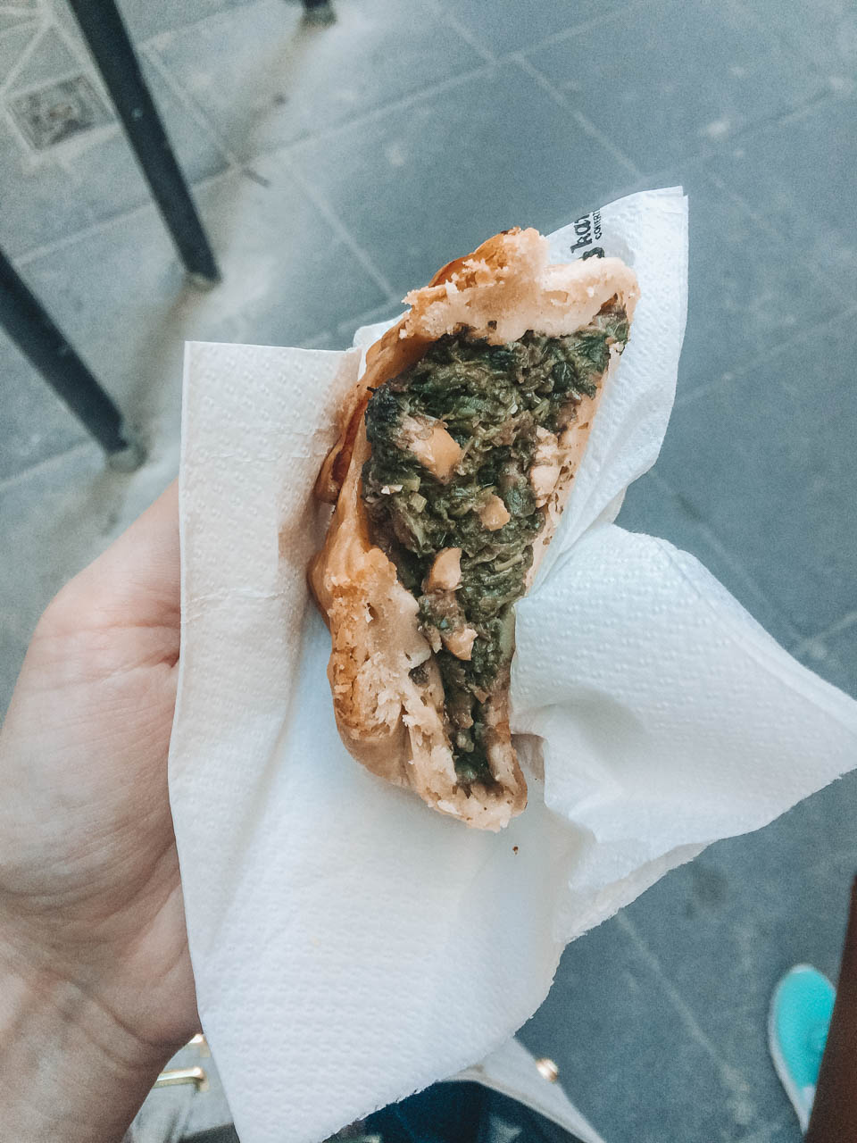 A girl holding a traditional Maltese qassatat with spinach