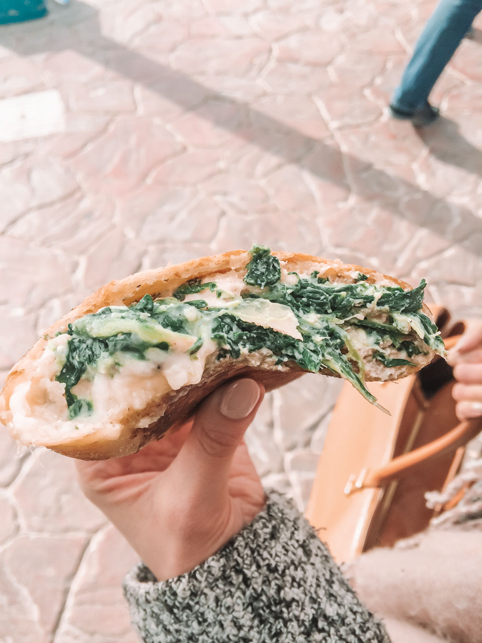 A girl holding a traditional Maltese pastry with spinach