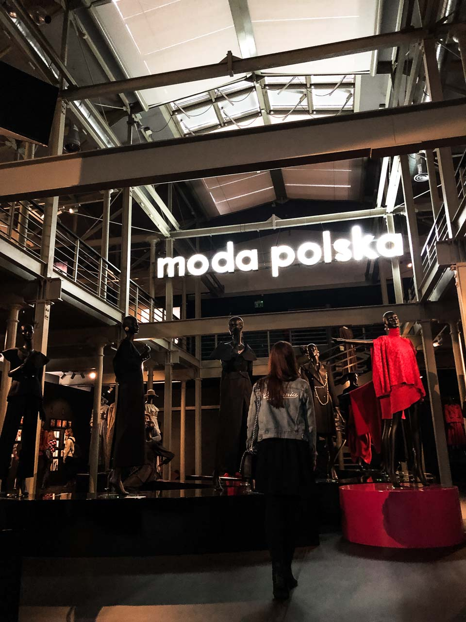 A girl in a denim jacket standing in front of the Moda Polska garments and neon sign displayed at The Central Museum of Textiles in Łódź, Poland