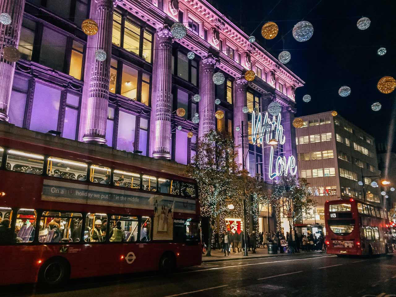 The exterior of Selfridges in London decorated for Christmas and a double-decker bus driving past