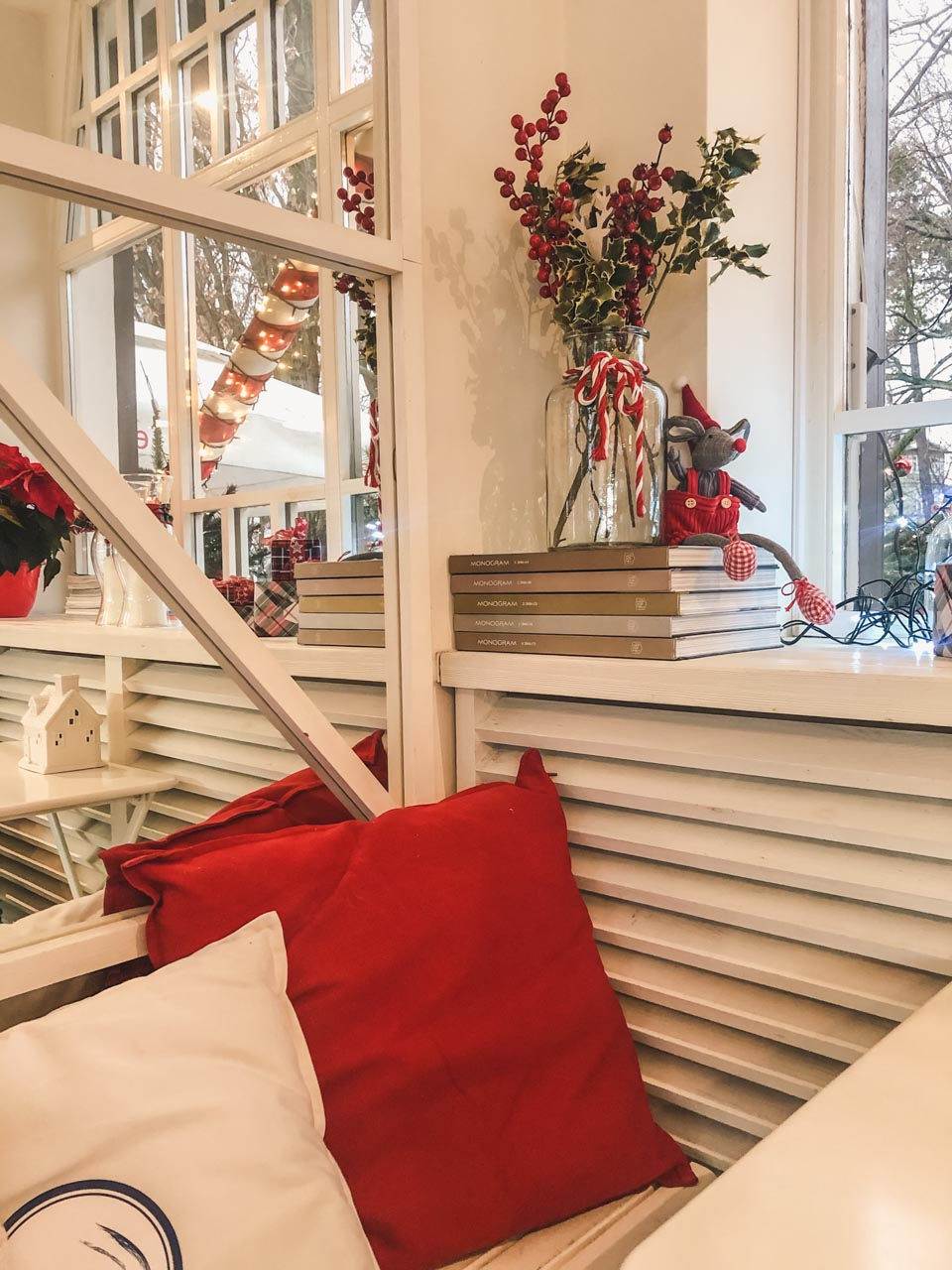 White and red pillows and Christmas decorations on a window sill