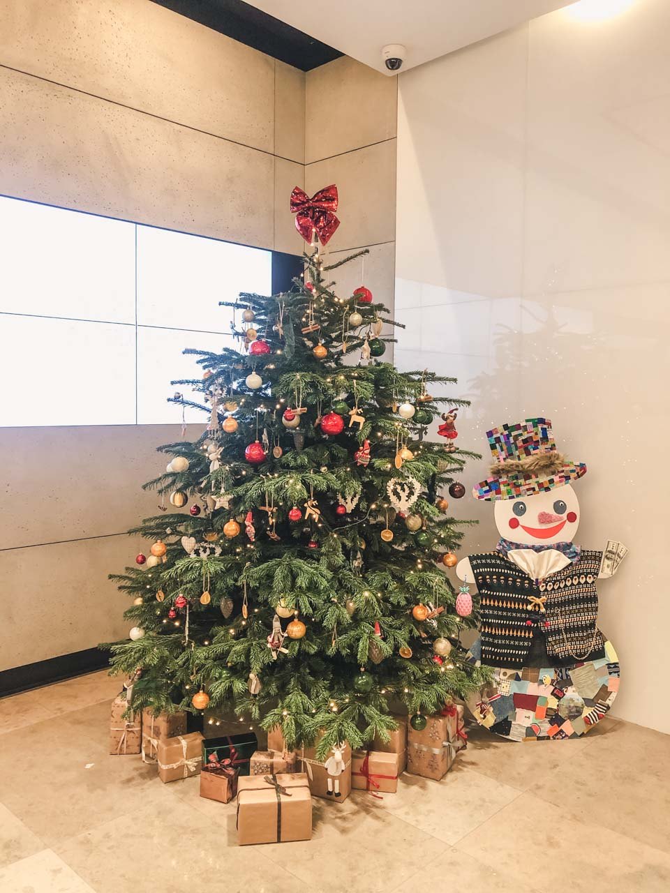 A decorated Christmas tree with presents underneath and a colourful snowman standing beside it