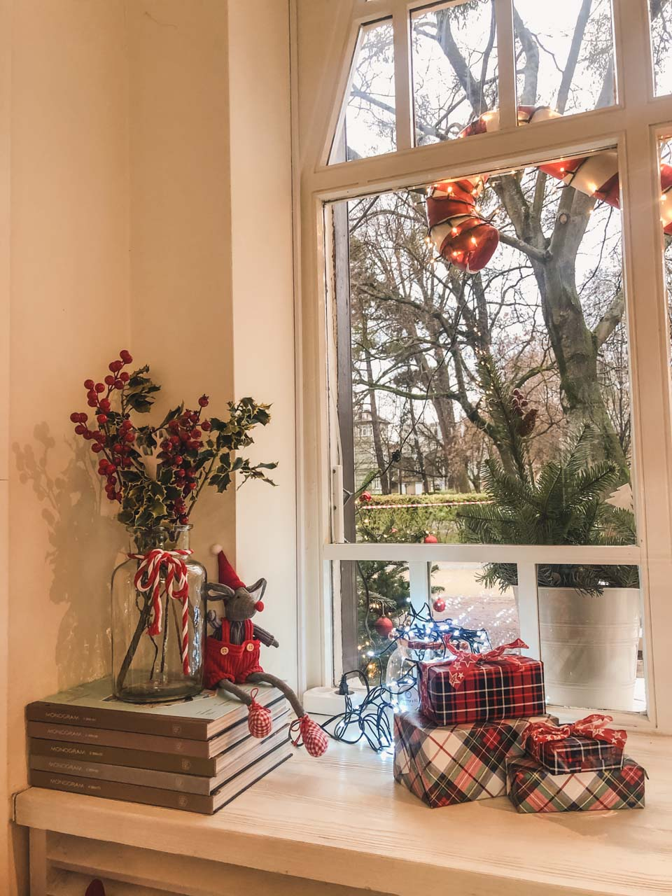 A couple of wrapped presents, a stack of books and a vase with holly on a window sill