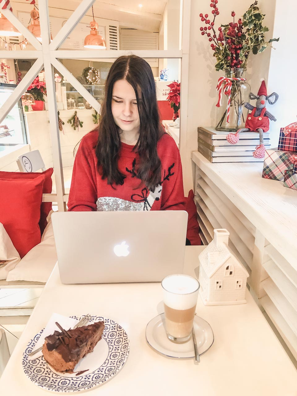 A girl typing something on her MacBook Air with a piece of cake and a cup of coffee placed beside her