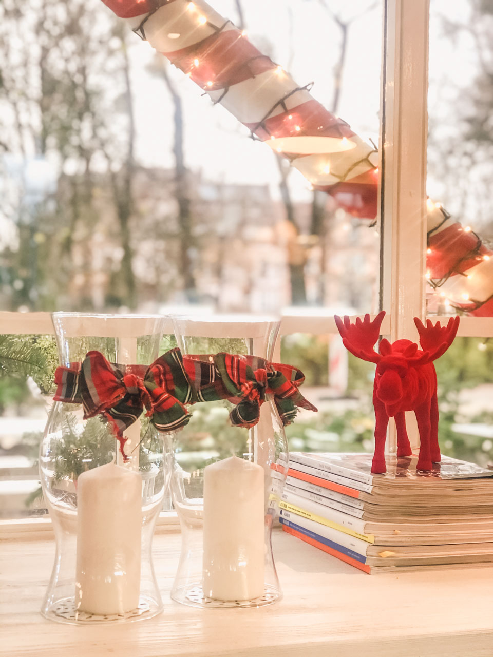 Festive candles and a reindeer figurine on a window sill