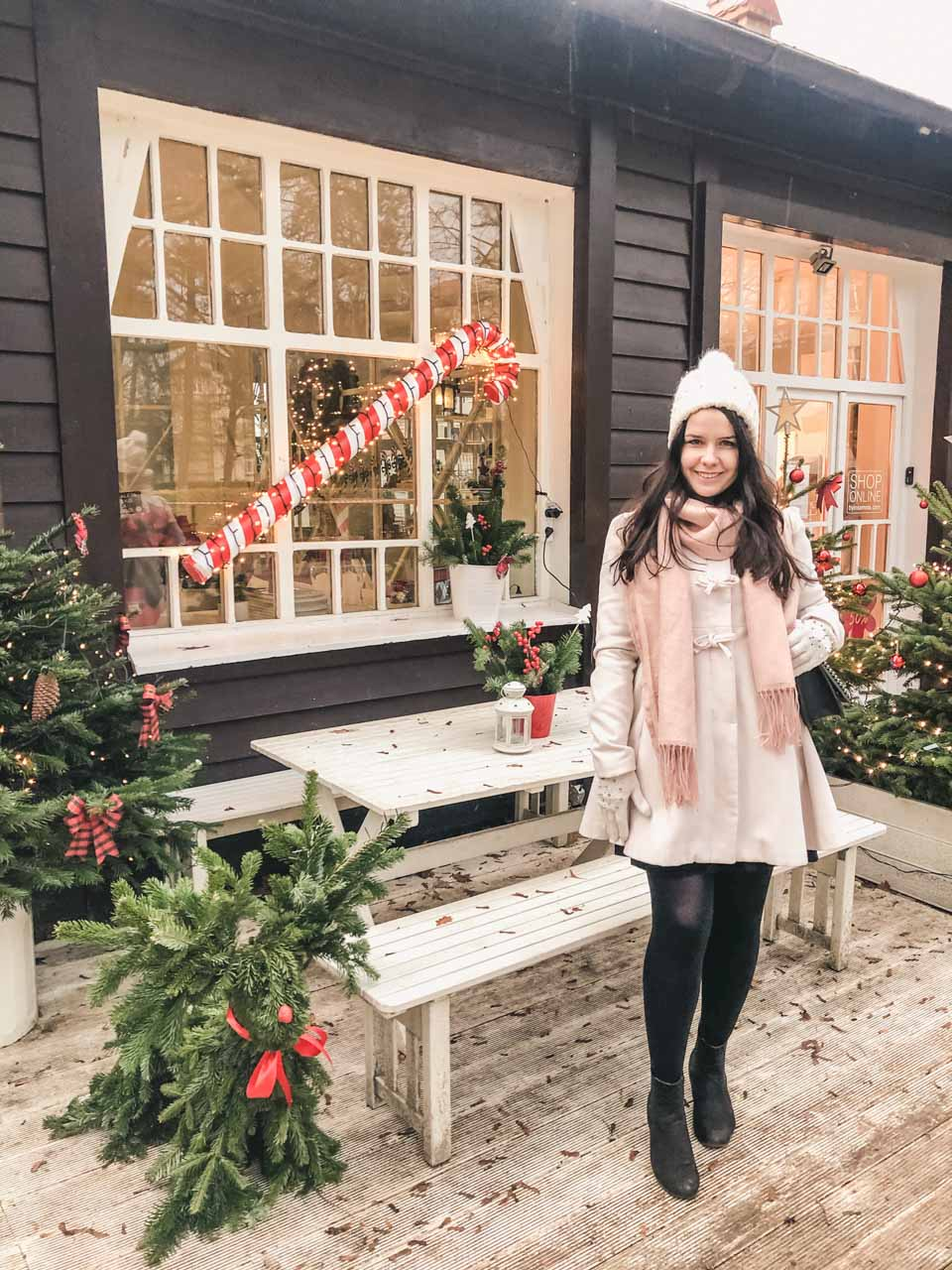 A girl in a white coat standing in front of Christmas trees and a decorative candy cane