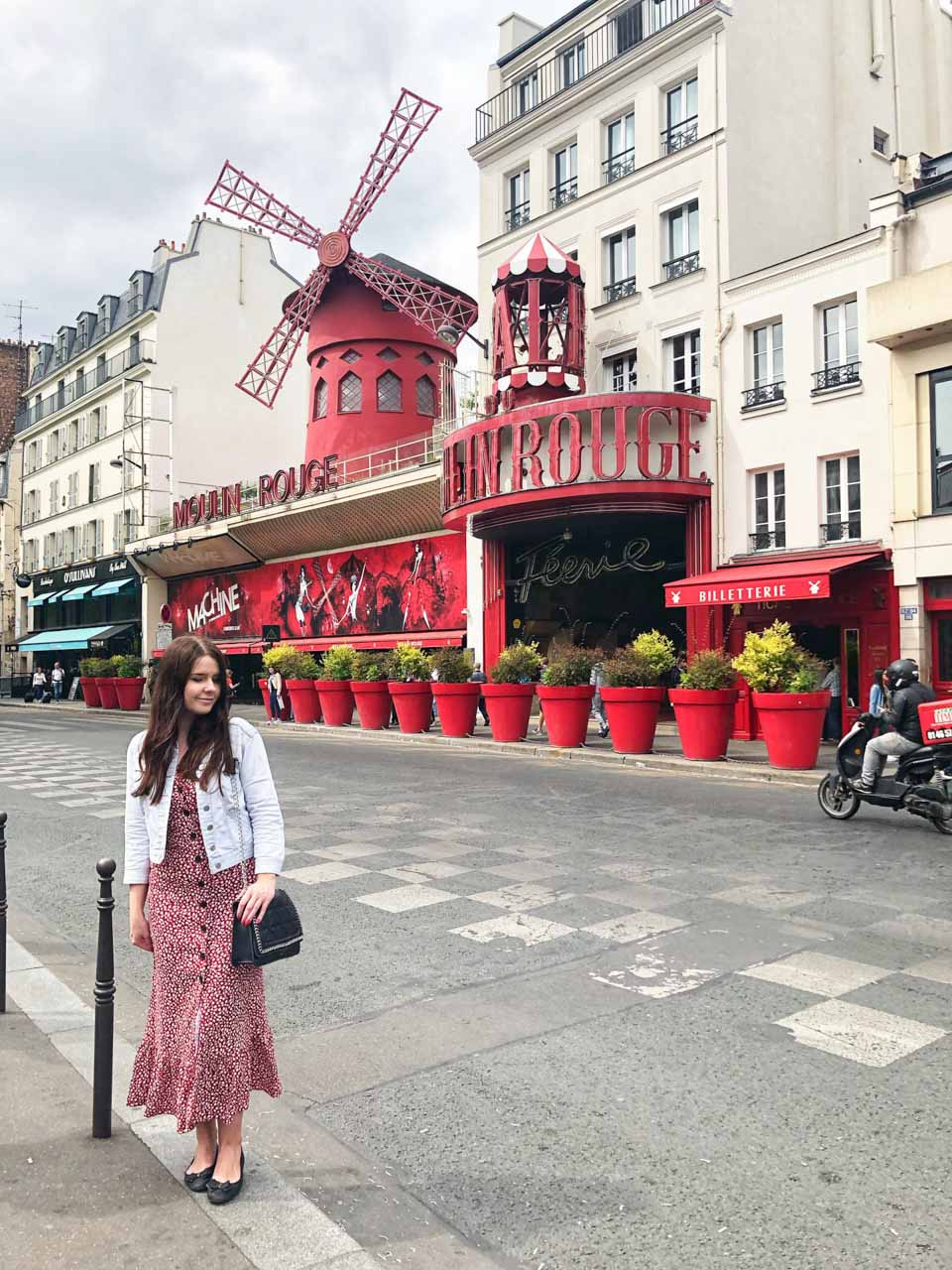 A girl in a red dress standing in front of the Moulin Rouge in Paris