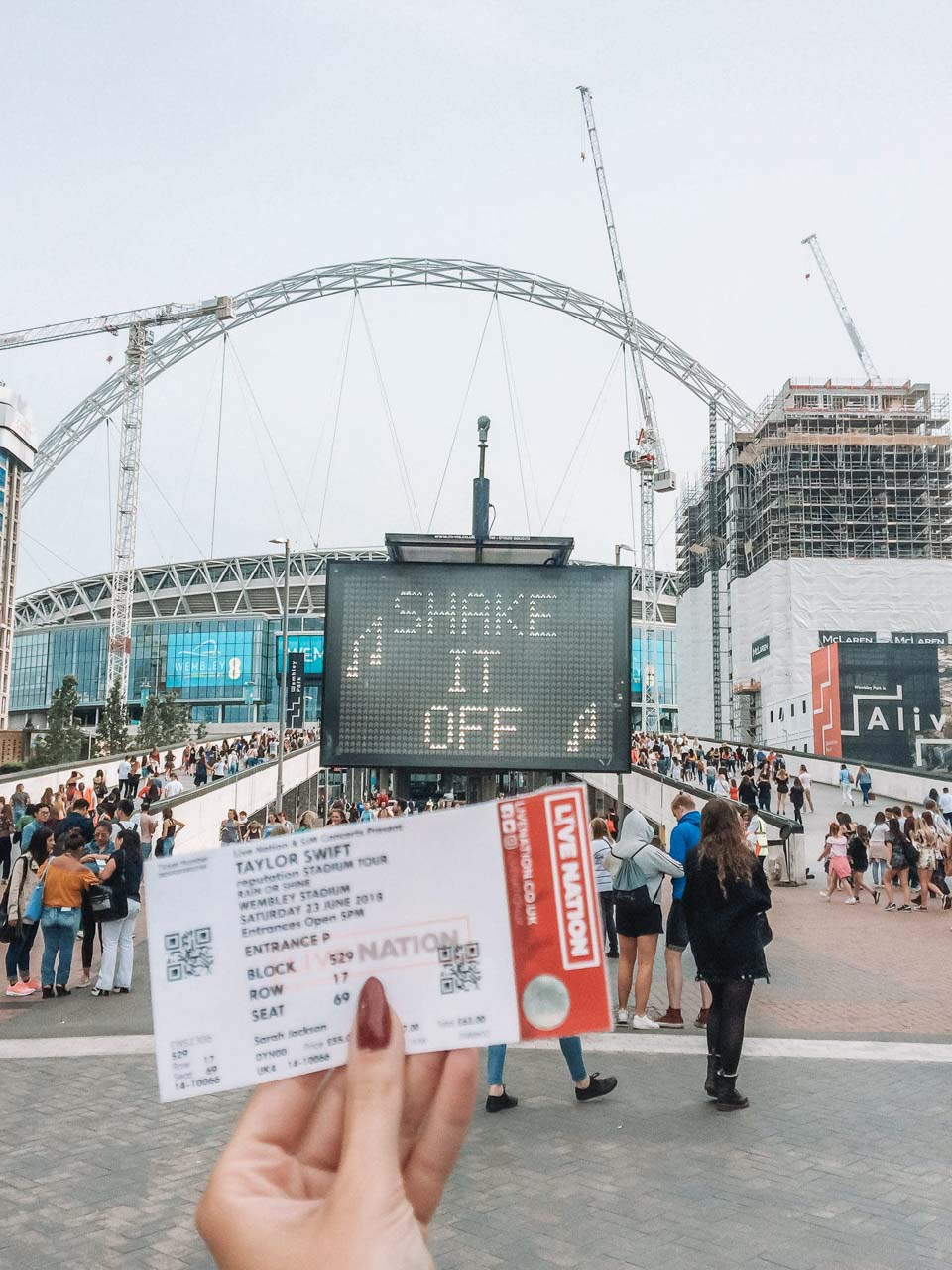A girl holding a Taylor Swift concert ticket outside the Wembley Stadium in London