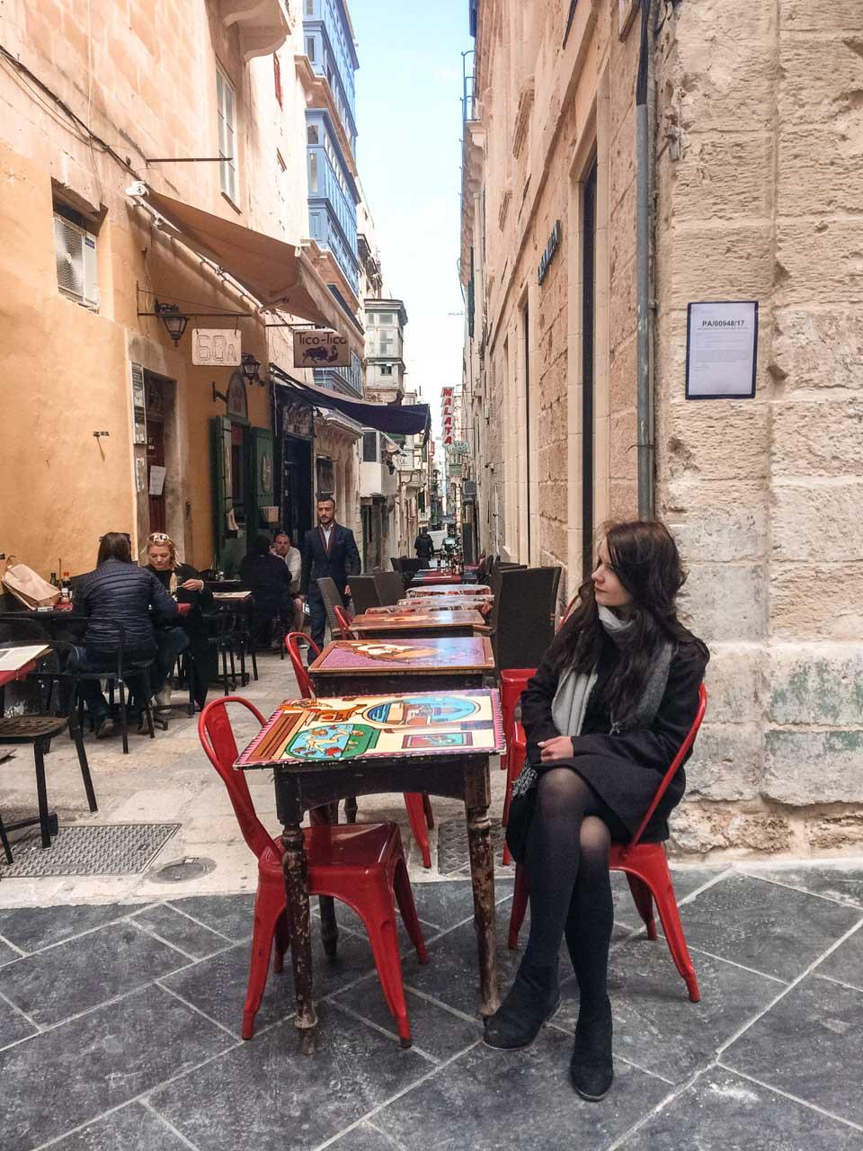 A girl sitting at a table on Strait Street in Valletta, Malta