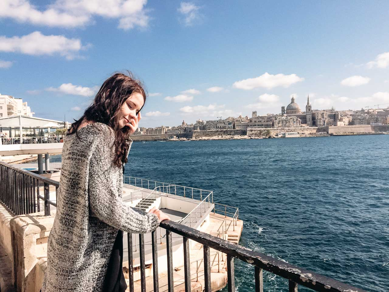 A girl standing on the promenade in Sliema, Malta with the Valletta skyline in the background